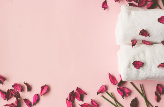 Towels, potpourri and scented sticks on pink background with copy space for your text; wellness or spa background