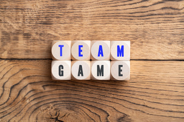 """cubes showing the message """"team game"""" on wooden background"""