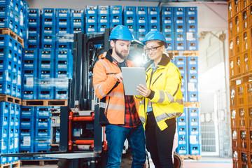 Mann und Frau als Arbeiter im Logistikzentrum nutzen Computer