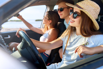 Friends rented a car for summer road trip to the beach. Female driver in glasses and straw hat having fun. Woman learned car driving and got a license. Girl wearing teeth braces. Travel lifestyle.