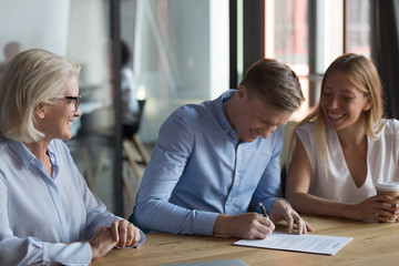 Confident businessman signing contract with partners, successful deal concept