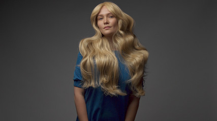 nordic blond model in studio with dramatic top light. jumping and showing gorgeous hair curls