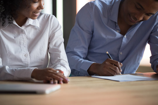 Close up African American man signing contract, successful deal