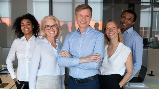 Successful team leader and diverse employees posing for photo together