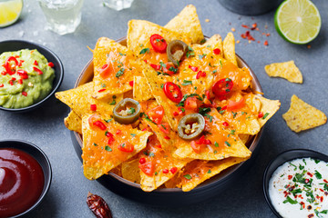 Nachos chips with melted cheese and dips variety in black bowl. Grey stone background.