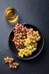 Fresh grape in bowl with white wine in glass on a black stone background. Top view.