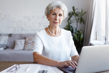 Picture of cheerful successful mature female blogger in her sixties sitting at her workplace with papers and laptop, keyboarding. Technology, communication, modern lifestyle and e-commerce concept