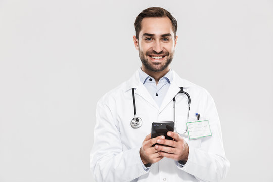 Portrait of kind young medical doctor with stethoscope working in clinic and holding cellphone