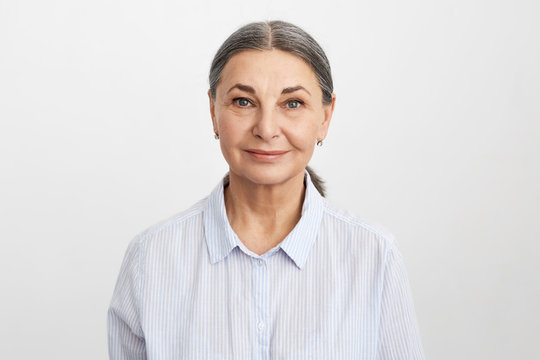 Isolated image of attractive friendly looking mature senior female employee with wrinkles, gray hair and blue eyes wearing formal shirt smiling confidently at camera, being ready for working day