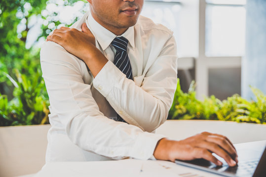 Businessman has neck pain, shoulder pain while woking with laptop. Office syndrome concept.