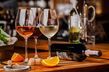Glasses of white, rose and red wine are on the table, a bottle and corks are nearby. Glasses are on the table in the bar in the restaurant. Background image. copy space