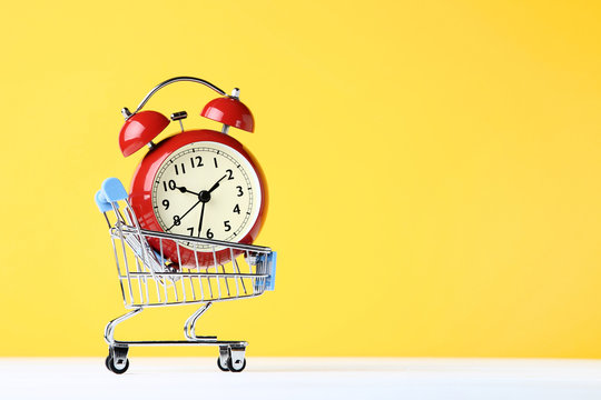 Small shopping cart with alarm clock on yellow background