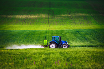 Wall Mural - Farming tractor plowing and spraying on field