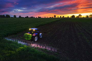 Tractor spraying field at spring