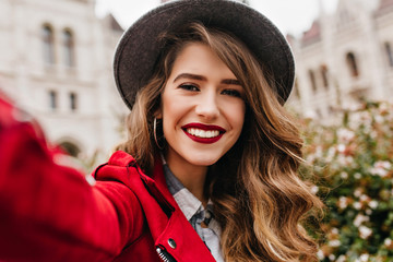 Close-up portrait of wonderful girl with light-brown hair making selfie during travel. Laughing european lady in fedora with red lips taking picture of herself while exploring old town.