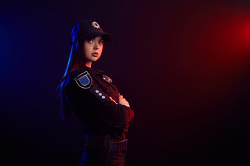 Serious female police officer is posing for the camera against a black background with red and blue backlighting.