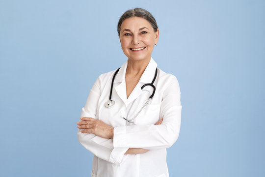 Isolated studio image of charismatic beautiful Caucasian senior female chief doctor crossing arms on her chest confidently and smiling broadly dressed in white overall with stethoscope around her neck