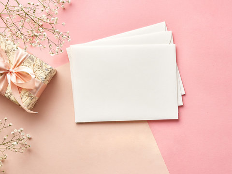 Mock up of blank envelopes on pink or beige background with flowers and present. View from the top.