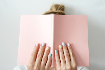 Stylish trendy color female manicure . Women s hands keep pink note pad