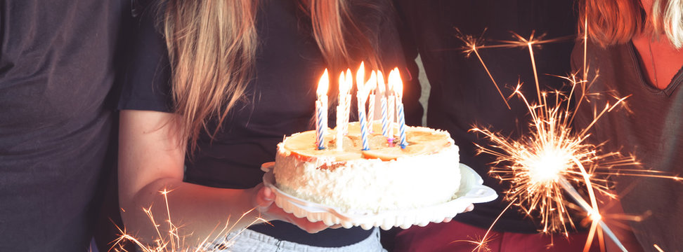 Teen girl blows out candles on a birthday cake with friends and family