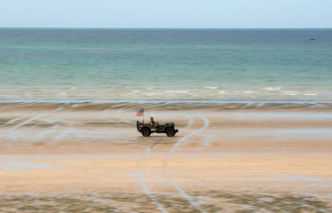 Enthusiasts enjoy a ride on a vintage army jeep during a re-enactment of D-Day landings in Arromanches