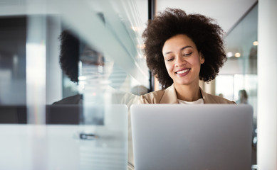 Wall Mural - Young african american woman working with tablet in office