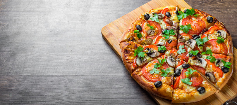 sliced Pizza with Mozzarella cheese, Tomatoes, pepper, olive, mushrooms, Spices and Fresh leaf. Italian pizza on wooden table background