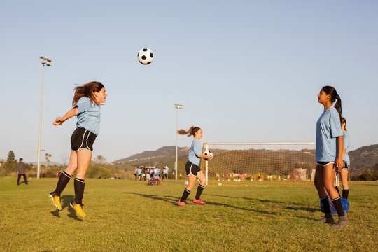 Side view of girls practicing soccer on grassy field against clear blue sky