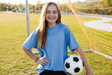 Portrait of smiling girl holding soccer ball in grassy field