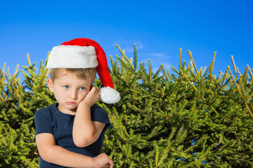 Boy in a red cap of Santa Claus is sad