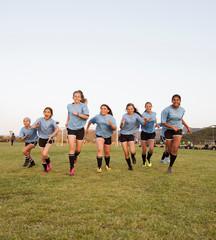 Girls running on soccer field against clear sky during sunset