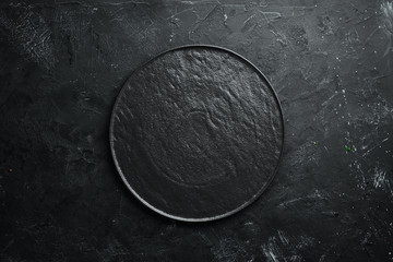 Round black stone plate. On a black stone background. Top view. Free space for your text. Wall mural