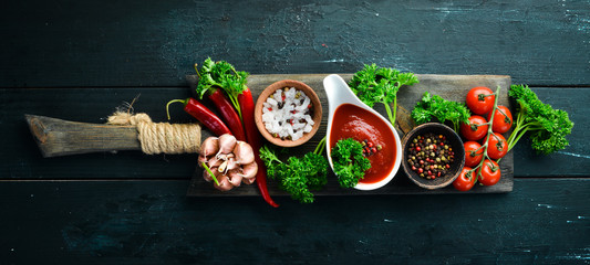 Set of red sauces on a wooden background. Ketchup, barbecue sauce, tomato sauce. Top view. Free space for your text.