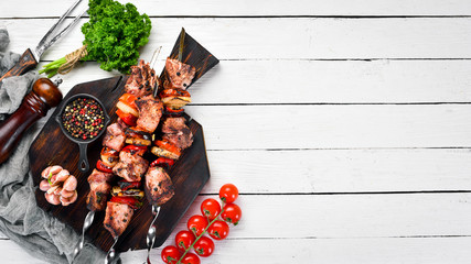 Pork shish kebab with onions and tomatoes. Barbecue. Top view. Free space for your text. Rustic style.