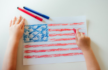 The child draws the flag of America.