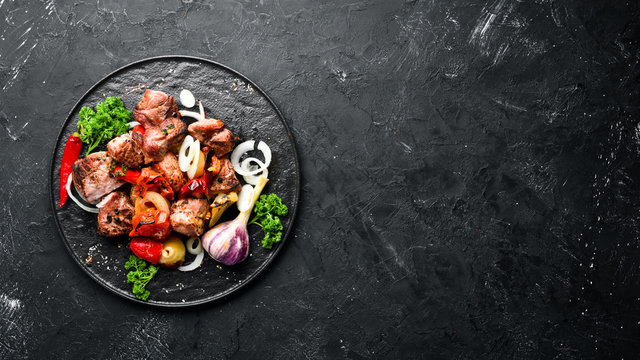 Kebab in a plate. Baked meat with onions and tomatoes. Barbecue. Top view. Free space for your text. Rustic style.