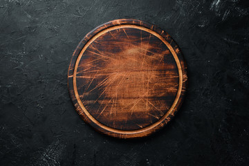 Old Wooden kitchen board on a black background. Top view. Free space for your text.