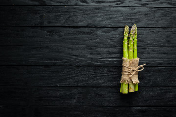 Fototapete - Green asparagus. Fresh asparagus on a black background. Top view. Free space for your text.