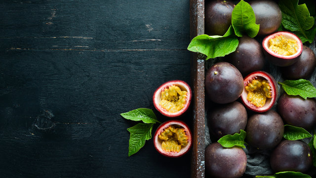Fresh passion fruit with leaves in Wooden Box. Tropical Fruits. Top view. Free space for text.