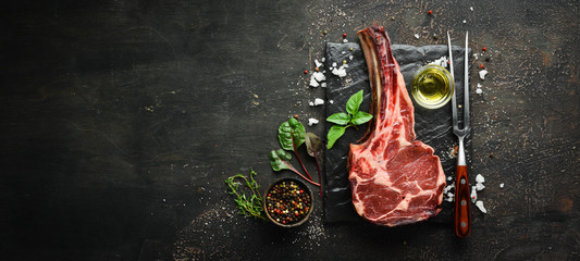 Printed roller blinds Steakhouse Raw dry steak tomahawk on a black background. Steak Cowboy. Barbecue. Top view. Free space for text.
