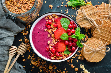 Smoothie bowl with granola, strawberry, red currants and mint. Breakfast. Top view. Free space for your text.