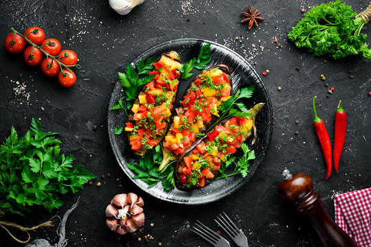 Eggplants baked with vegetables on a black plate. Top view. Free space for your text.