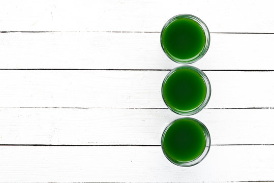Healthy green wheat drink on a white background. Top view. Free space for your text.
