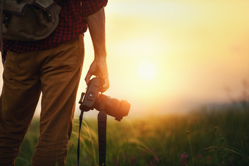 travel photographer. man traveler with camera  at sunset in nature