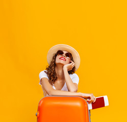 Obraz concept of travel. happy woman girl with suitcase and  passport on  yellow background. - fototapety do salonu