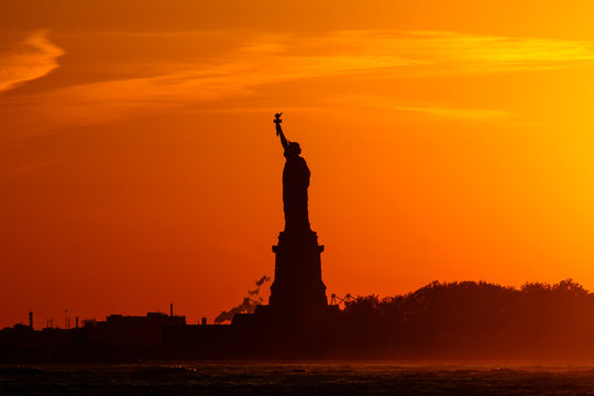 statue of liberty at sunset with silhouette and orange sky