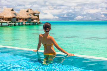 Luxury overwater bungalow hotel room with infinity swimming pool woman looking at blue ocean view. Tropical travel summer vacation lifestyle.