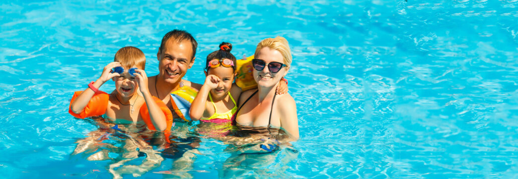 Happy family with two kids having fun in the swimming pool. Summer vacation concept