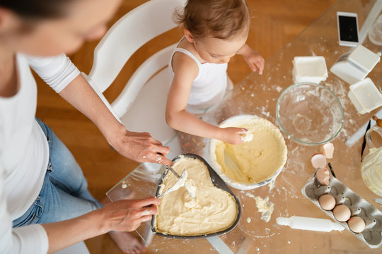 Top view of mother and little daughter making a cake together in kitchen at home