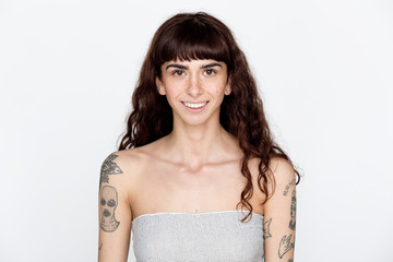 Portrait of smiling young woman with freckles and tattoos on her upper arms